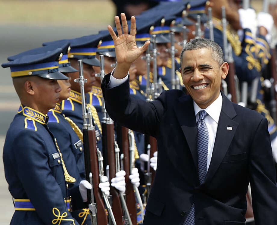 U.S. President Barack Obama waves to the media upon arrival, Monday, April 28, 2014, at the Ninoy Aquino International Airport in Manila, Philippines. Trade and security are expected to be discussed in Obama's state visit to the Philippines. (AP Photo/Bullit Marquez)