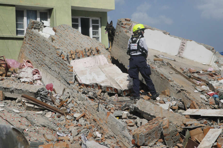 A rescue worker from USAID along with a sniffer dog looks for survivors at the site of a building that collapsed in an earthquake in Kathmandu, Nepal, Tuesday, May 12, 2015. A major earthquake has hit Nepal near the Chinese border between the capital of Kathmandu and Mount Everest less than three weeks after the country was devastated by a quake. (AP Photo/Niranjan Shrestha)