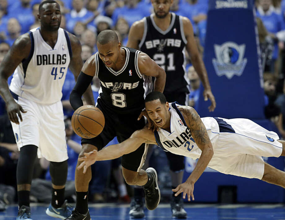 San Antonio Spurs' Patty Mills (8) charges up court after grabbing a loose ball as Dallas Mavericks' Devin Harris (20) attempts to slap it away in the second half of Game 4 of an NBA basketball first-round playoff series, Monday, April 28, 2014, in Dallas. The Spurs won 93-89. (AP Photo/Tony Gutierrez)