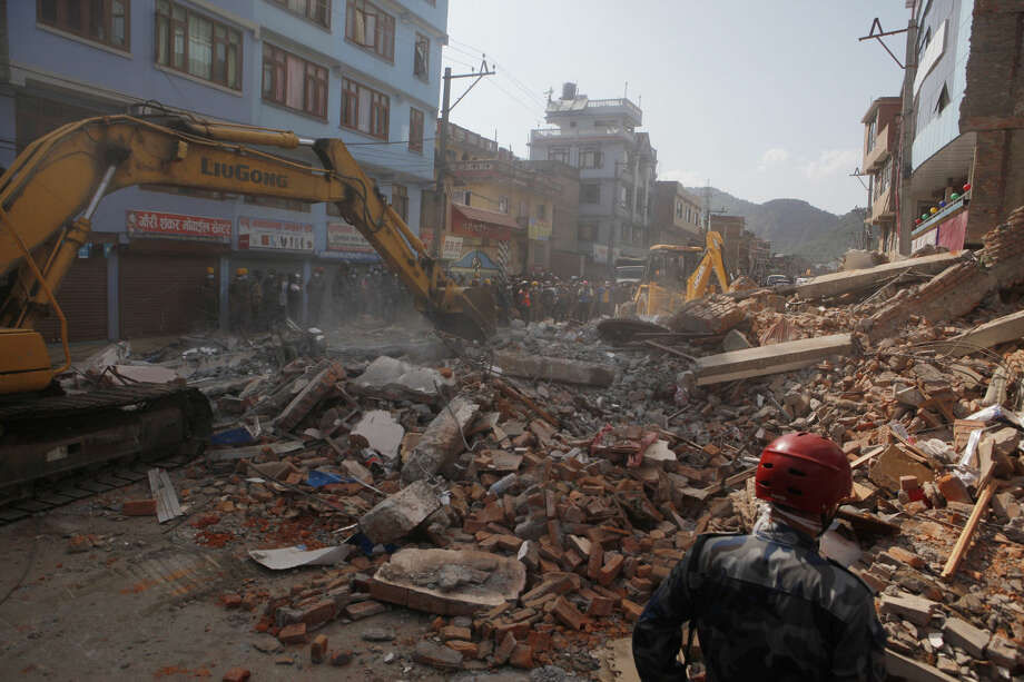 Earthmovers clear the debris at the site of a building that collapsed in an earthquake in Kathmandu, Nepal, Tuesday, May 12, 2015. A major earthquake has hit Nepal near the Chinese border between the capital of Kathmandu and Mount Everest less than three weeks after the country was devastated by a quake. (AP Photo/Niranjan Shrestha)