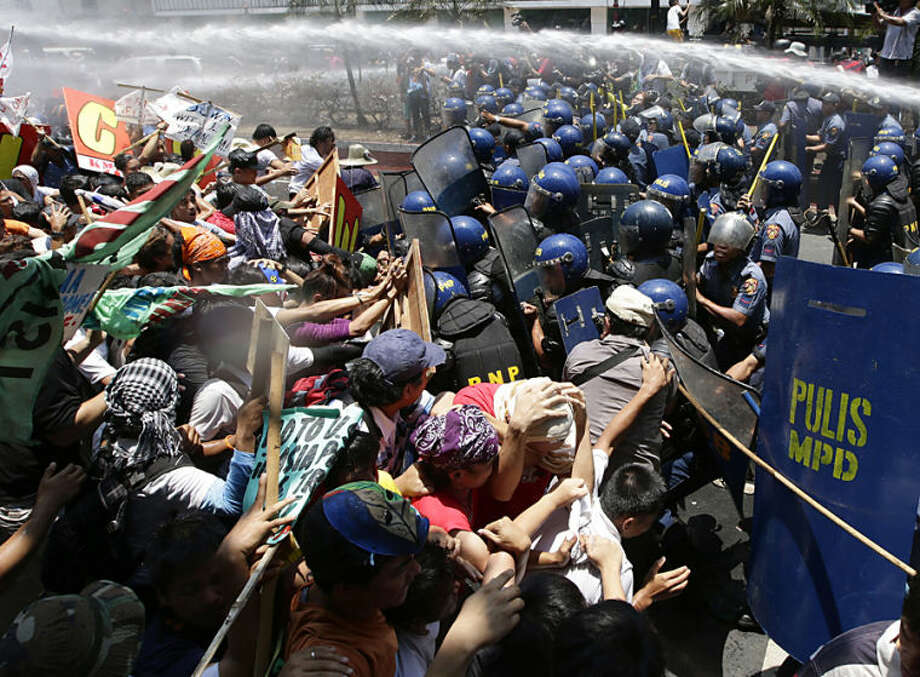"""Protesters clash with police while trying to surge towards the U.S. Embassy in Manila to protest U.S. President Barack Obama's first ever state visit to the Philippines Tuesday, April 29, 2014. Obama vigorously defended his foreign policy record Monday, arguing that his cautious approach to global problems has avoided the type of missteps that contributed to a """"disastrous"""" decade of war for the United States. The Philippines is the last leg of Obama's four-nation Asia tour. (AP Photo/Bullit Marquez)"""