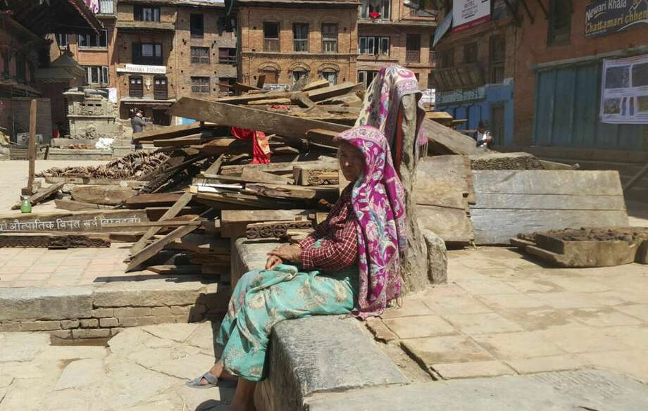 A Nepalese woman sits outdoors after another earthquake in Bhaktapur, Nepal, Tuesday, May 12, 2015. A major earthquake has hit Nepal near the Chinese border between the capital of Kathmandu and Mount Everest less than three weeks after the country was devastated by a quake. (AP Photo/Tashi Sherpa)