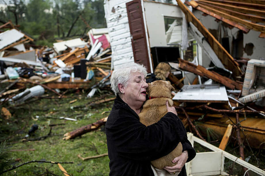 Constance Lambert embraces her dog after finding it alive when returning to her destroyed home in Tupelo, Miss., Monday, April 28, 2014. Lambert was at an event away from her home when the tornado struck and rushed back to check on her pets. (AP Photo/The Commercial Appeal, Brad Vest)