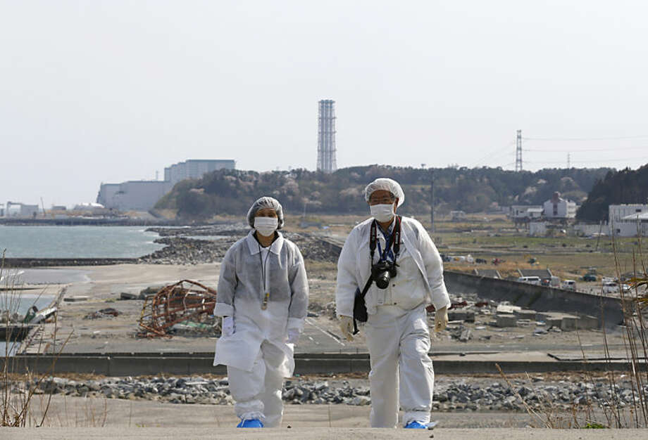 In this photo taken Thursday, April 17, 2014, Kazuhiro Onuki, right, and his wife, Michiko, wearing white protective gears and filtered masks, walk along the coast damaged by the 2011 tsunami against a backdrop of Fukushima Dai-ni Nuclear Power Plant, that stands south of the crippled Fukushima Dai-ichi nuclear plant, in Tomioka, Fukushima Prefecture, northeastern Japan. It's difficult to imagine ever living again in Tomioka, a ghost town about 10 kilometers (6 miles) from the former Dai-ichi nuclear plant. And yet. More than three years after meltdowns at the plant forced this community of 16,000 people to flee, Onuki can't quite make the psychological break to start anew. (AP Photo/Shizuo Kambayashi)