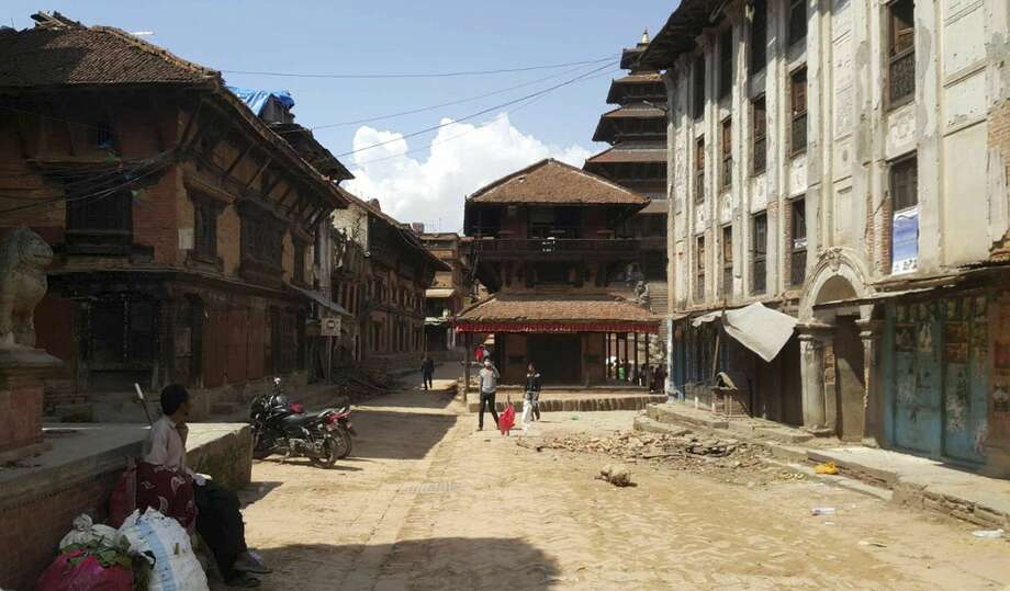 A man sits as Nepalese people walk through a street after another earthquake in Bhaktapur, Nepal, Tuesday, May 12, 2015. A major earthquake has hit Nepal near the Chinese border between the capital of Kathmandu and Mount Everest less than three weeks after the country was devastated by a quake. (AP Photo/Tashi Sherpa)