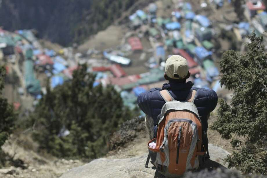 In this April 6, 2015 file photo, a local Nepalese man sits above Namche, a village inhabited by mainly Sherpas, in the Everest region in Nepal. A major earthquake has hit Nepal near the Chinese border between the capital of Kathmandu and Mount Everest less than three weeks after the country was devastated by a quake (AP Photo/Tashi Sherpa, file)