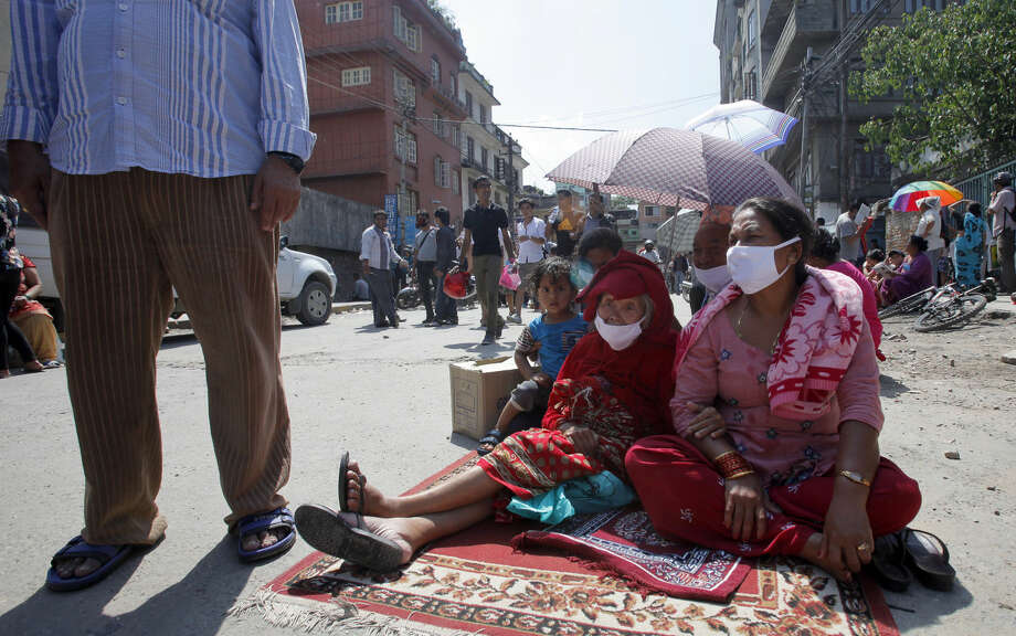 Nepalese people take refuge on a street after an earthquake hit Kathmandu, Nepal, Tuesday, May 12, 2015. A major earthquake hit Nepal in a remote region near the Chinese border on Tuesday, less than three weeks after the country was ravaged by another deadly quake. (AP Photo/Bikram Rai)