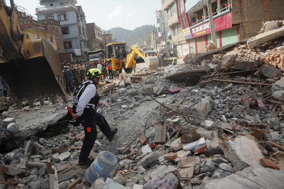 A rescue worker from USAID inspects the site of a building that collapsed in an earthquake in Kathmandu, Nepal, Tuesday, May 12, 2015. A major earthquake has hit Nepal near the Chinese border between the capital of Kathmandu and Mount Everest less than three weeks after the country was devastated by a quake. (AP Photo/Niranjan Shrestha)