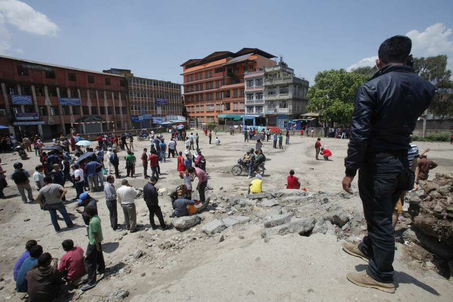 Nepalese people gather in an open area after a second earthquake hit Nepal in Kathmandu, Nepal, Tuesday, May 12, 2015. A major earthquake hit a remote mountainous region of Nepal on Tuesday, triggering landslides and toppling buildings less than three weeks after the country was ravaged by another deadly quake. (AP Photo/Bikram Rai)