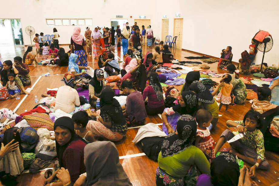 Migrants rest at a temporary immigration detention center in Langkawi, Malaysia Tuesday, May 12, 2015. Hundreds of migrants abandoned at sea by smugglers in Southeast Asia have reached land and relative safety in the past two days. But an estimated 6,000 Bangladeshis and Rohingya Muslims from Myanmar remain trapped in crowded, wooden boats, migrant officials and activists said. (AP Photo/Vincent Thian)