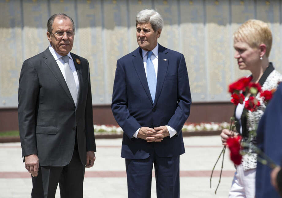 U.S Secretary of State John Kerry and Russian Foreign Minister Sergey Lavrov, left, watch as members of the United States and Russian delegations place red flowers at the Zakovkzalny War Memorial in Sochi, Russia, Tuesday May 12, 2015. Kerry is in Russia to meet President Vladimir Putin with an eye on easing badly strained relations over conflicts in Ukraine and Syria. (Joshua Roberts/Pool Photo via AP)