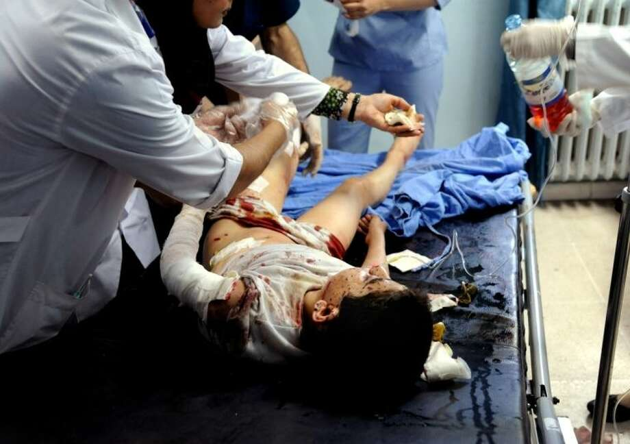 In this photo which AP obtained from the Syrian official news agency SANA, and has been authenticated based on its contents and other AP reporting, doctors treat a wounded Syrian boy at a hospital in Damascus, Syria, Tuesday, April 29, 2014. A series of mortar shells slammed into central Damascus on Tuesday, killing more than a dozen people and wounding scores, state media reported. The attacks in the Syrian capital came a day after President Bashar Assad announced his candidacy for the June 3 presidential election. (AP Photo/SANA)