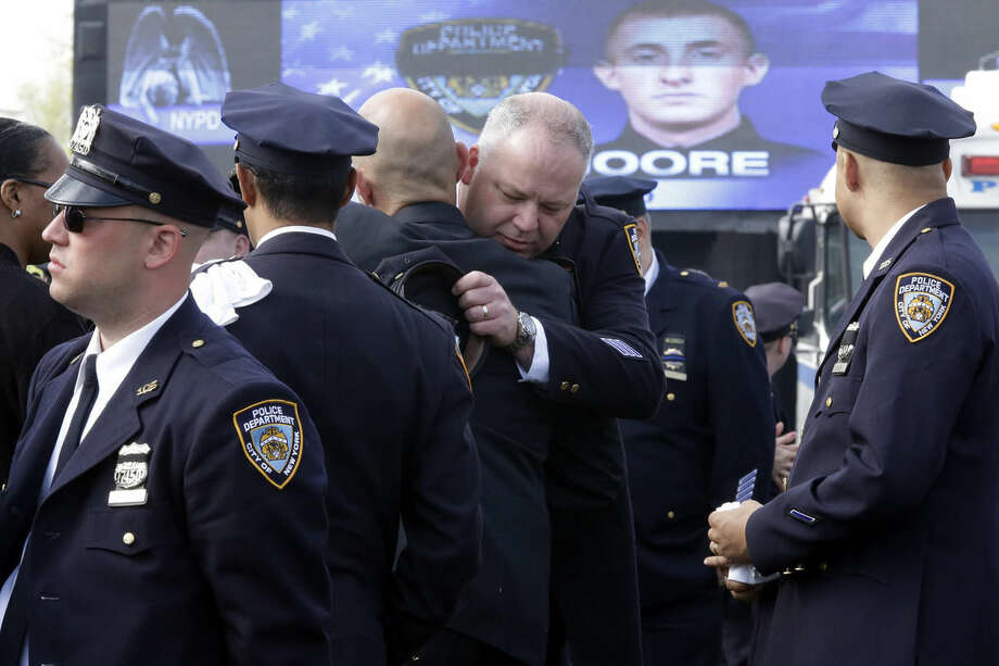 A couple of police officers embrace as they arrive for the funeral mass of New York City police officer Brian Moore, Friday, May 8, 2015, at the St. James Roman Catholic church in Seaford, N.Y. As many as 30,000 police officers from across the United States are expected to pay their respects at the Long Island funeral for Moore, who died Monday after being shot in the head while on duty two days earlier in Queens. AP Photo/Mary Altaffer)