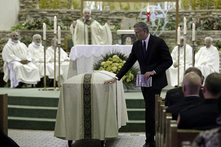 New York City Mayor Bill de Blasio touches the casket of New York City Police officer Brian Moore, at the Saint James Roman Catholic Church, in Seaford, NY, Friday, May 8, 2015. As many as 30,000 police officers from across the United States are expected to pay their respects at the Long Island funeral for the 25-year-old officer slain on patrol. (AP Photo/Richard Drew, Pool)