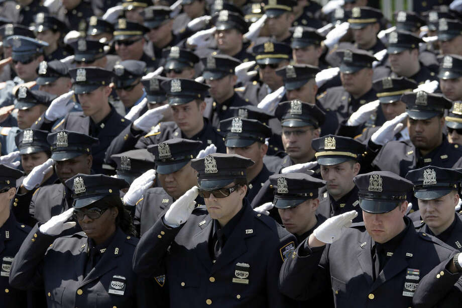 Police officers salute as the procession for New York City Police officer Brian Moore passes after his funeral mass, Friday, May 8, 2015, at the St. James Roman Catholic church in Seaford, N.Y. The 25-year-old died Monday, two days after he was shot in Queens. (AP Photo/Mary Altaffer)