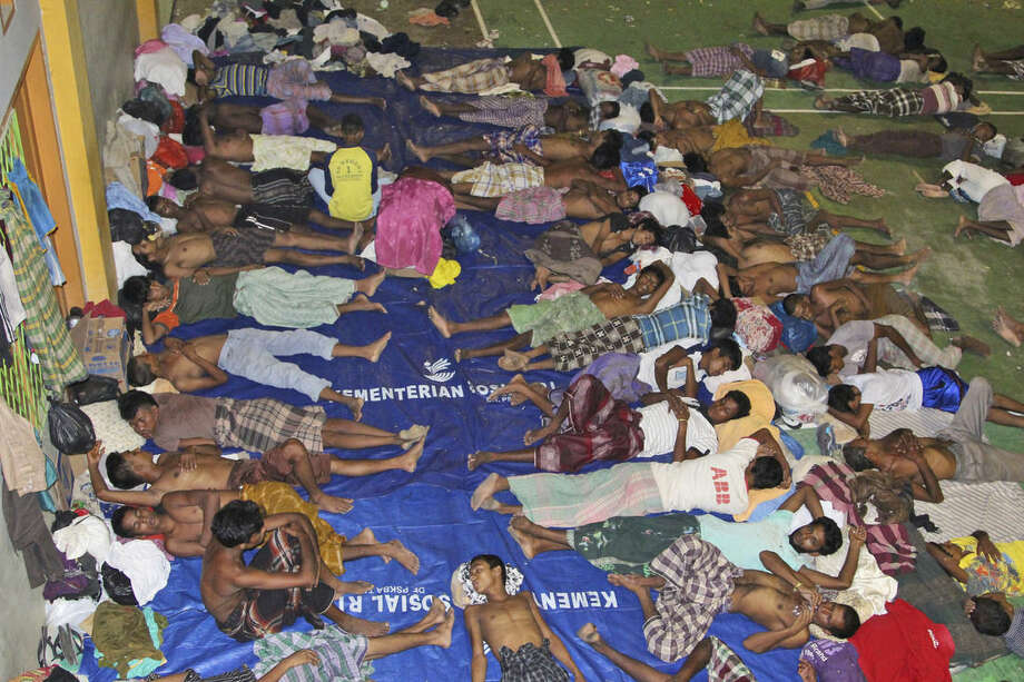 Migrants sleep on the floor at a sports stadium that was turned into a temporary shelter in Lhoksukon, Aceh province, Indonesia, Tuesday, May 12, 2015. Hundreds of migrants abandoned at sea by smugglers in Southeast Asia have reached land and relative safety in the past two days. But an estimated 6,000 Bangladeshis and Rohingya Muslims from Myanmar remain trapped in crowded, wooden boats, migrant officials and activists said. With food and clean water running low, some could be in grave danger. (AP Photo/S. Yulinnas)