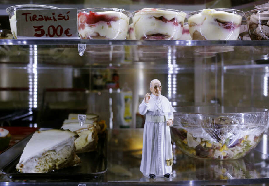 A statuette of Pope Francis is placed among desserts on sale at a cafe, in St. Peter's Square at the Vatican, Sunday, April 27, 2014. Tens of thousands of people have filled St. Peter's Square for a historic day of four popes, with Popes Francis and Benedict XVI honoring John XXIII and John Paul II by declaring them saints in the first ever canonization of two pontiffs. (AP Photo/Alessandra Tarantino)