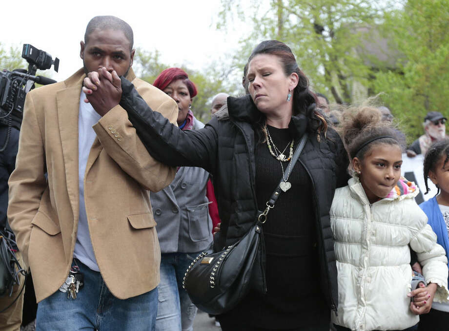 Jeff Jackson, left, comforts his girlfriend, Andrea Irwin, the mother of Tony Robinson, while escorting her during a protest march on Williamson Street, Tuesday, May 12, 2015, in Madison, Wis. Dane County District Attorney Ismael Ozanne announced Tuesday that Madison Police Officer Matt Kenny would not face charges for the shooting death of Robinson. (M.P. King/Wisconsin State Journal via AP)