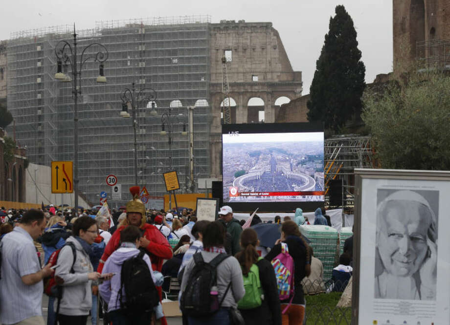 People follow the ceremony for the canonizations of Pope John XXIII and Pope John Paul II taking place at the Vatican on giant screens set up at the Colosseum, in Rome, Sunday, April 27, 2014. Pope Francis declared Popes John XXIII and John Paul II (on a large drawing at right) saints before some 800,000 people on Sunday in an unprecedented ceremony.(AP Photo/Riccardo De Luca)