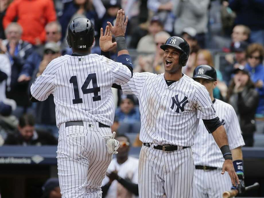New York Yankees' Aaron Hicks, right, celebrates with teammate Starlin Castro (14) after they scored on a double by Carlos Beltran during the fifth inning of a baseball game against the Boston Red Sox Saturday, May 7, 2016, in New York. (AP Photo/Frank Franklin II)