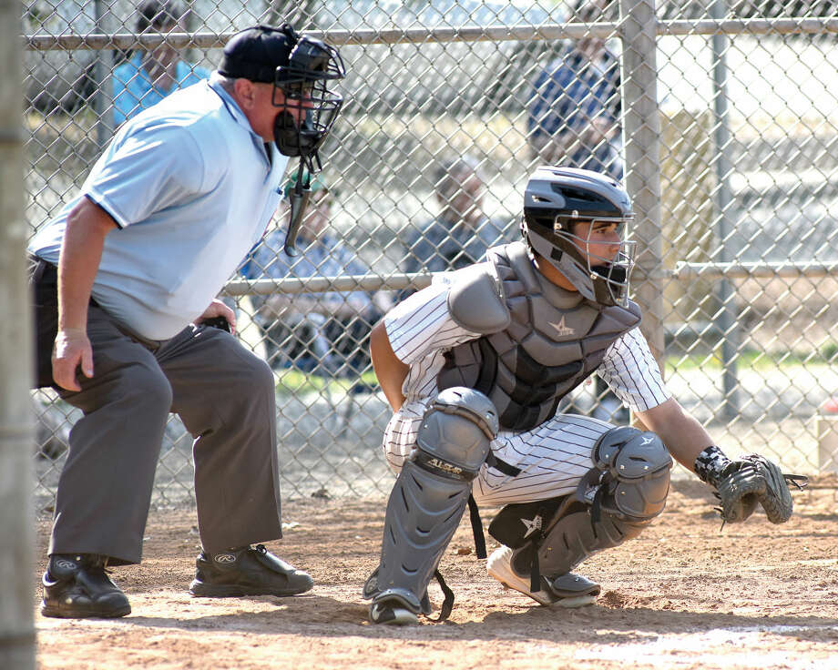 Home plate umpire Bob Victory, left, and Norwalk catcher Marco Monteiro await the next pitch during Monday's game against Stamford. (Hour photo/John Nash)