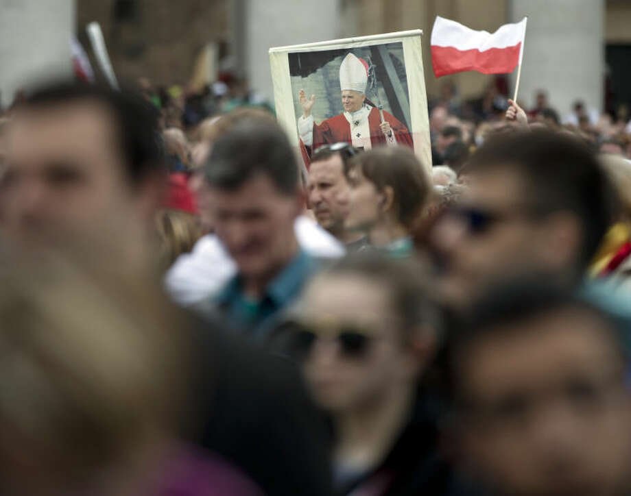 People hold a picture of Pope John Paul II in St. Peter's Square at the Vatican, Sunday, April 27, 2014. Pope Francis has declared his two predecessors John XXIII and John Paul II saints in an unprecedented canonization ceremony made even more historic by the presence of retired Pope Benedict XVI. (AP Photo/Vadim Ghirda)