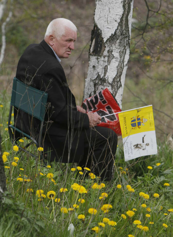 A man with a yellow-and-white papal flag sits on the meadows in front of of God's Mercy sanctuary, in Krakow, Poland, Sunday, April 27, 2014, when Pope Francis declared Polish-born Pope John II a saint. Thousands of people gathered in Krakow to watch live the Vatican ceremony. (AP Photo/Czarek Sokolowski)