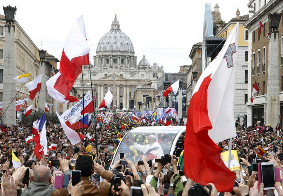 Pope Francis greets faithful as he is driven through the crowd along Via della Conciliazione after celebrating the ceremony for the canonizations of Pope John XXIII and Pope John Paul II in St. Peter's Square, at the Vatican, Sunday, April 27, 2014. Pope Francis declared his two predecessors John XXIII and John Paul II saints before some 800,000 people on Sunday, an unprecedented ceremony made even more historic by the presence in St. Peter's Square of emeritus Pope Benedict XVI. (AP Photo/Riccardo De Luca)