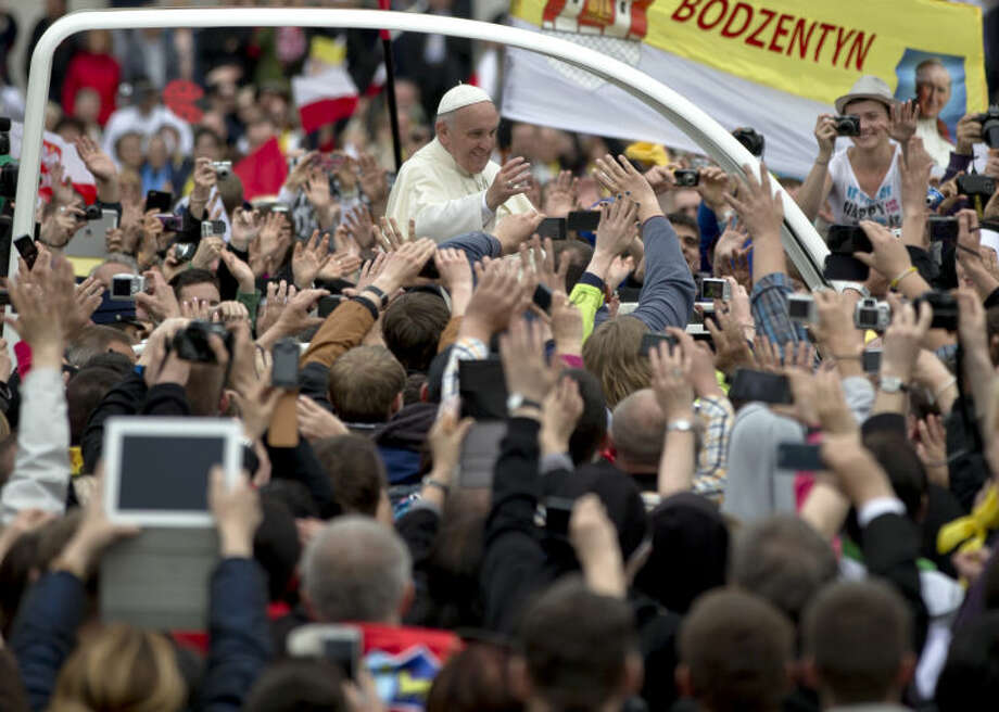 Pope Francis is driven through the crowd in St. Peter's Square at the Vatican, Sunday, April 27, 2014. Pope Francis has declared his two predecessors John XXIII and John Paul II saints in an unprecedented canonization ceremony made even more historic by the presence of retired Pope Benedict XVI. (AP Photo/Vadim Ghirda)