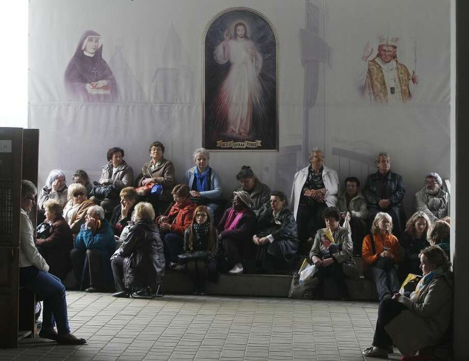Faithful attentively are listening in front of God's Mercy sanctuary in Krakow, Poland, Sunday, April 27, 2014, to Pope Francis as he declares Polish-born Pope John Paul II a saint in a Vatican ceremony. Thousands of people gathered to watch live the ceremony. (AP Photo/Czarek Sokolowski)