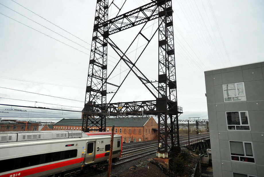 A Metro-North train heading east crosses Walk Bridge in Norwalk. The bridge passes close to a building at right, and is near a number of businesses and structures that some fear could be impacted by replacement plans.