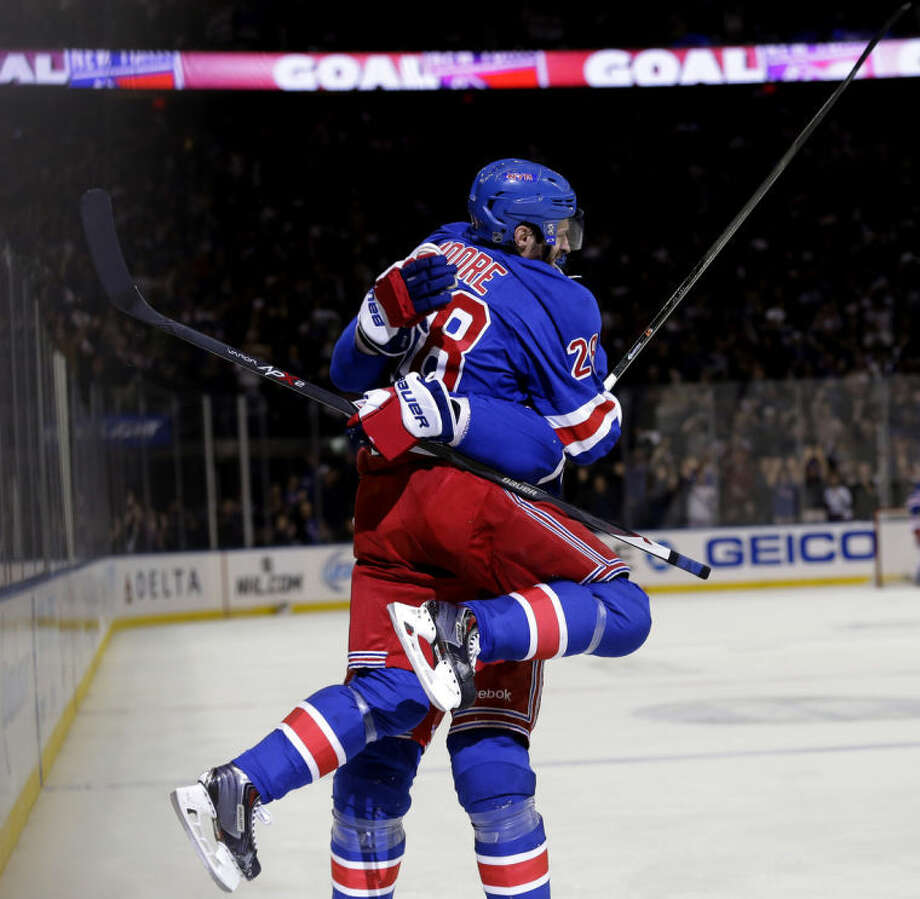 New York Rangers' Dominic Moore, top, jumps into teammate Brian Boyle's arms to celebrate his goal during the second period of Game 5 of an NHL hockey first-round playoff series against the Philadelphia Flyers, Sunday, April 27, 2014, in New York. (AP Photo/Seth Wenig)