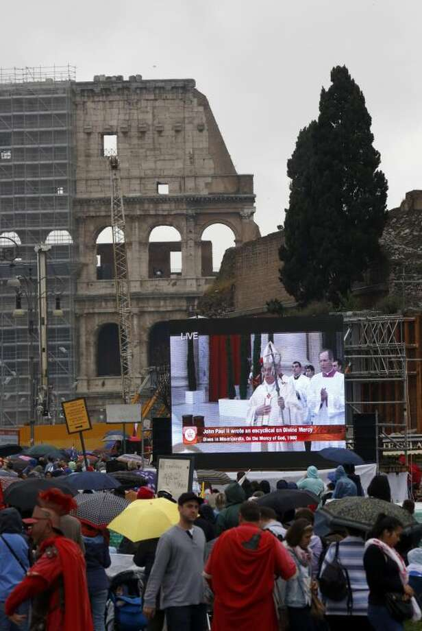 People watch at the ceremony for the canonizations of Pope John XXIII and Pope John Paul II taking place at the Vatican on giant screens set up at the Colosseum, in Rome, Sunday, April 27, 2014. Pope Francis declared Popes John XXIII and John Paul II saints before some 800,000 people on Sunday in an unprecedented ceremony.(AP Photo/Riccardo De Luca)