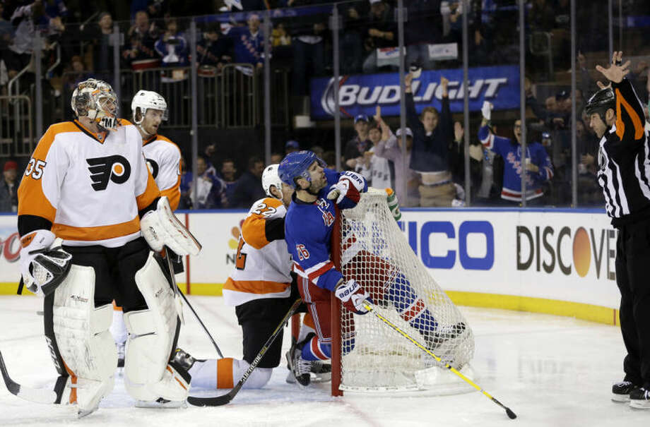 Philadelphia Flyers goalie Steve Mason, left, and New York Rangers' Martin St. Louis, center, looks up at a referee, right, who rules that St. Louis did not score during the second period of Game 5 of an NHL hockey first-round playoff series on Sunday, April 27, 2014, in New York. (AP Photo/Seth Wenig)
