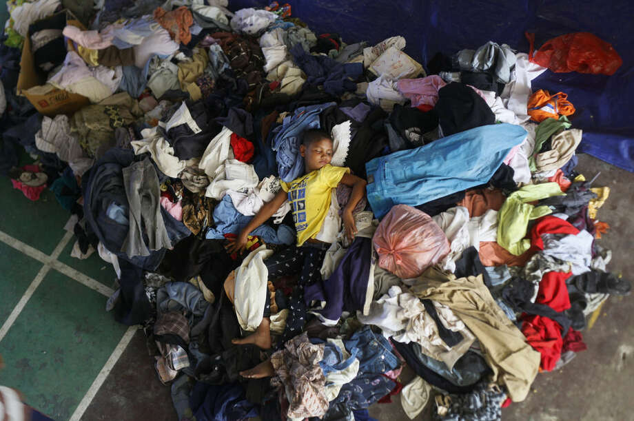 An ethnic Rohingya boy sleeps on a pile of used clothing donated by local residents at a sports stadium turned into temporary shelter for migrants whose boats washed ashore on Sumatra island on Sunday, in Lhoksukon, Aceh province, Indonesia, Wednesday, May 13, 2015. Abandoned at sea, thousands of Bangladeshis and members of Myanmar's long-persecuted Rohingya Musilm minority appear to have no place to go after two Southeast Asian nations refused to offer refuge to boatloads of hungry men, women and children. (AP Photo/Binsar Bakkara)