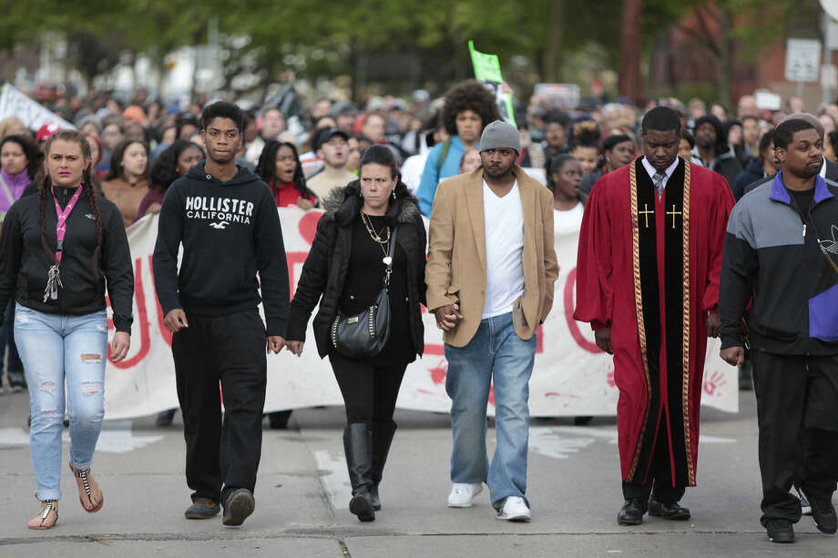 Andrea Irwin, center, mother of Tony Robinson, and her boyfriend, Jeff Jackson, center right, participate in a protest march on Williamson Street, Tuesday, May 12, 2015, in Madison, Wis. Dane County District Attorney Ismael Ozanne announced Tuesday that Madison Police Officer Matt Kenny would not face charges for the shooting death of Robinson. (M.P. King/Wisconsin State Journal via AP)