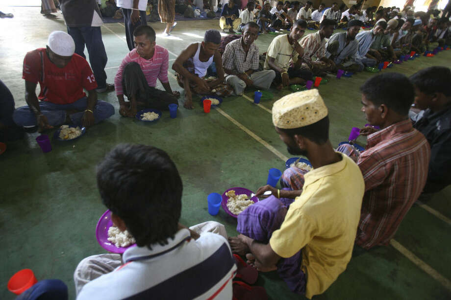 Ethnic Rohingya men have their breakfast at a sports stadium turned into temporary shelter for migrants whose boats washed ashore on Sumatra island on Sunday, in Lhoksukon, Aceh province, Indonesia, Wednesday, May 13, 2015. Abandoned at sea, thousands of Bangladeshis and members of Myanmar's long-persecuted Rohingya Musilm minority appear to have no place to go after two Southeast Asian nations refused to offer refuge to boatloads of hungry men, women and children. (AP Photo/Binsar Bakkara)