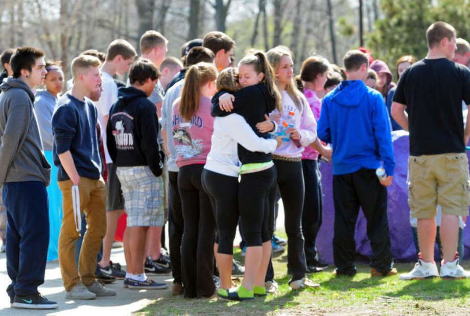 Students hug and spray paint a rock purple outside Jonathan Law High School in Milford, Conn., Friday, April 25, 2014, in memory of 16-year-old stabbing victim Maren Sanchez. Sanchez was stabbed to death earlier in the day during an altercation inside the school. A teenage boy is in custody, and police are investigating whether she was stabbed because she declined to be his date at the junior prom. (AP Photo/The New Haven Register, Peter Hvizdak) MANDATORY CREDIT