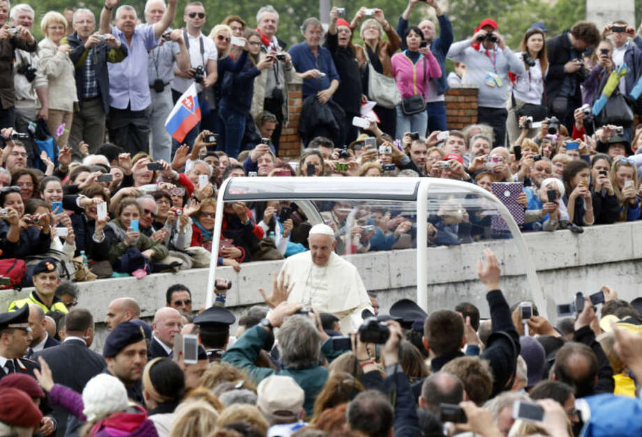 Pope Francis is driven away in his popemobile after celebrating the ceremony for the canonizations of Pope John XXIII and Pope John Paul II in St. Peter's Square at the Vatican, in Rome, Sunday, April 27, 2014. Pope Francis declared Popes John XXIII and John Paul II saints before some 800,000 people on Sunday in an unprecedented ceremony. (AP Photo/Riccardo De Luca)