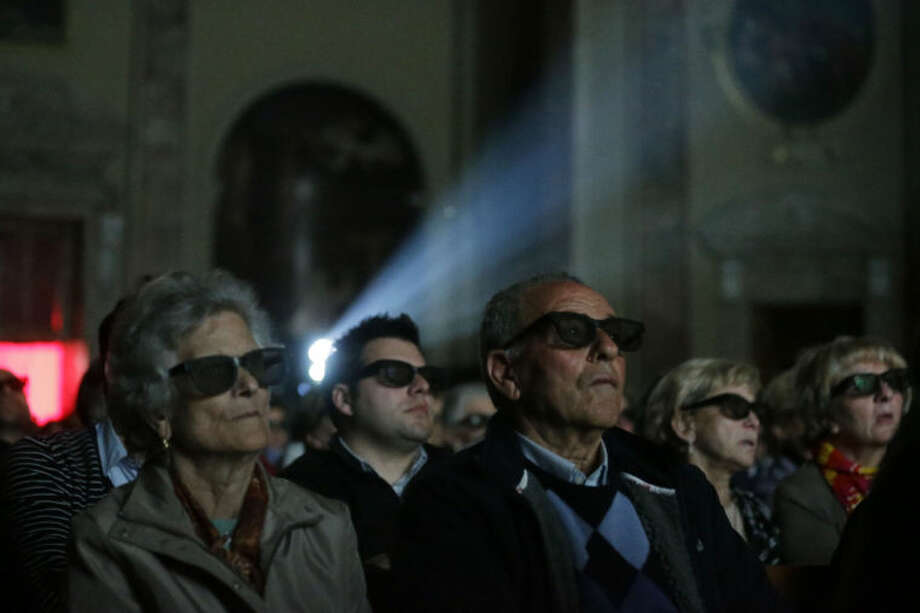 Faithful wear 3D glasses as they watch the screening of the canonization of Pope John XXIII and Pope John Paul II taking place at the Vatican, at the parish church in Sotto il Monte Giovanni XXIII, near Bergamo, northern Italy, the town of John XXIII, Sunday, April 27, 2014. Pope Francis declared his two predecessors John XXIII and John Paul II saints on Sunday before hundreds of thousands of people in St. Peter's Square, an unprecedented ceremony made even more historic by the presence of retired Pope Benedict XVI. (AP Photo/Luca Bruno)