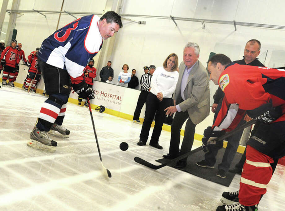 Norwalk Mayor Harry Rilling drops the puck in the ceremony to begin the Pucks For Prevention Charity Hockey Game to benefit the Children's Connection Sunday at the SONO Ice House in Norwalk. From left is Norwalk police officer Lt. Tim Murphy, Kari Pesavento program director with The Children's Connection, Police Chief Thomas E. Kulhawik and a member of the Danbury police department opposing Norwalk. Hour photo/Matthew Vinci