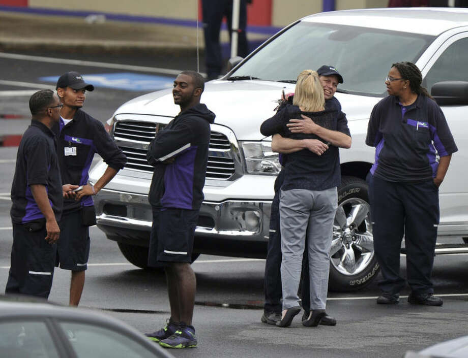 """FedEx Employees and family members gather a skating rink following a shooting at the FedEx facility in Kennesaw, Ga., on Tuesday, April 29, 2014. A shooter described as being armed with an assault rifle and having bullets strapped across his chest """"like Rambo"""" opened fire Tuesday morning at a FedEx station outside Atlanta, wounding at least six people before police found the suspect dead from an apparent self-inflicted gunshot. (AP Photo/Atlanta Journal-Constitution, Brant Sanderlin) MARIETTA DAILY OUT; GWINNETT DAILY POST OUT; LOCAL TV OUT; WXIA-TV OUT; WGCL-TV OUT ."""