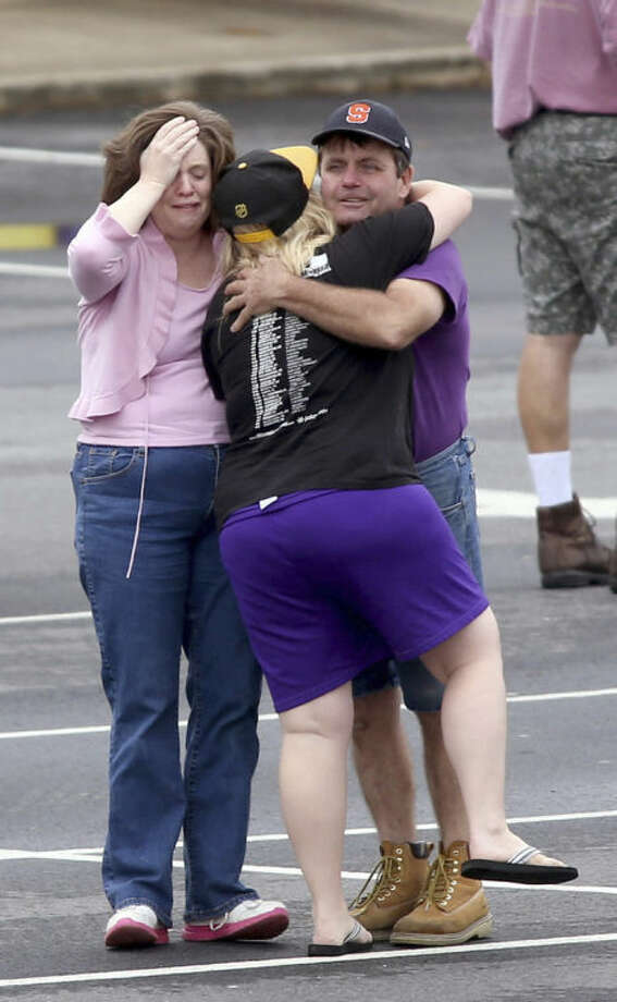 A FedEx employee, right, is consoled as other FedEx employees wait to meet their family at a nearby business after they were evacuated from the Airport Road FedEx facility after an early morning shooting Tuesday April 29, 2014, in Kennesaw, Ga. At least six people were wounded before police swarmed the facility. The shooter was found dead from an apparent self-inflicted gunshot wound. (AP Photo/Jason Getz)