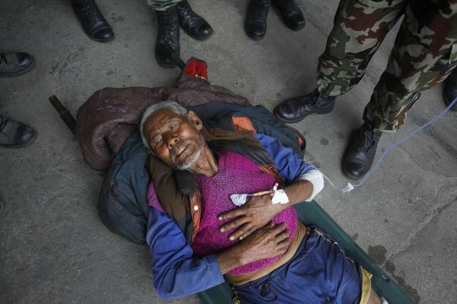 A Nepalese person injured in Tuesday's earthquake brought from Charikot, Dolakha District lies on a stretcher at the Tribhuvan International Airport in Kathmandu, Nepal, Wednesday, May 13, 2015. Thousands of fear-stricken people spent the night out in the open as a new earthquake killed dozens of people and spread more misery in Nepal, which is still struggling to recover from a devastating quake nearly three weeks ago. (AP Photo/Niranjan Shrestha)