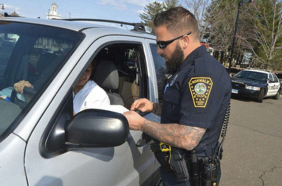 Alex von Kleydorff/Hearst Connecticut MediaNorwalk Police Officer David Geismar issues a ticket to a driver who was on her cell phone during a recent distracted driving enforcement.