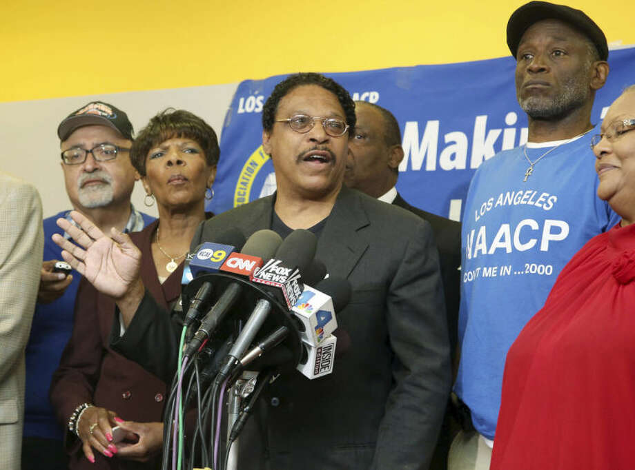 Leon Jenkins, center, president of the Los Angeles chapter of the NAACP, announces that Los Angeles Clippers owner Donald Sterling will not be receiving his lifetime achievement award, at a news conference in Culver City, Calif., Monday, April 28, 2014. The Clippers owner allegedly made racially charged comments in a recorded conversation. Sterling had been slated to receive the honor on May 15 as part of the 100th anniversary celebration of the group's Los Angeles chapter. (AP Photo/Nick Ut)