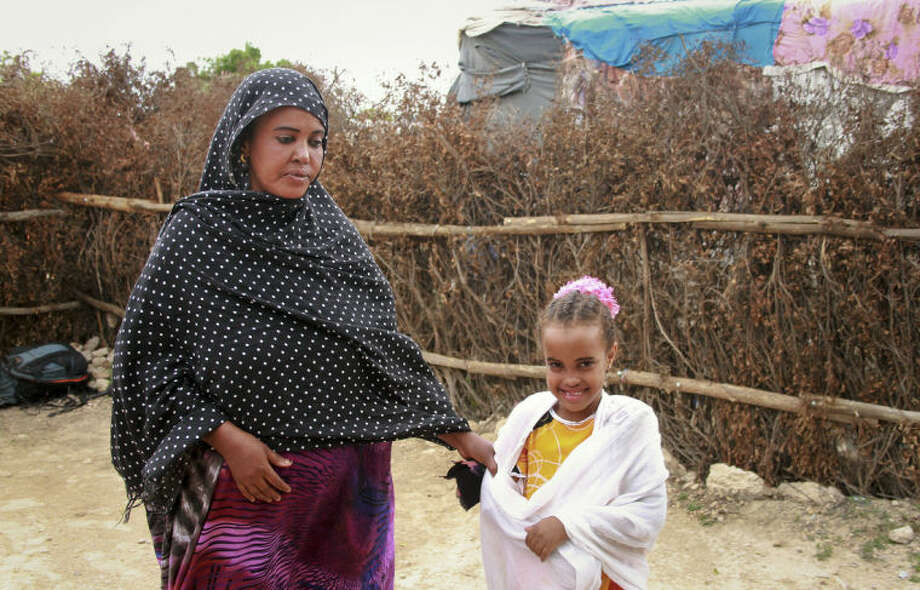 In this photo taken Sunday, April 27, 2014, Ubah Mohammed Abdule, 33, left, walks with her daughter Neshad Yusuf Ahmed, 5, right, outside her hut in the Shedder refugee camp near the town of Jigjiga, in far eastern Ethiopia. The Somali mother's home is a small shelter with a frame of sticks covered by ragged blankets on the dusty grounds of a refugee camp but it was to her that her 15-year-old son Yahya Abdi wanted to travel to on an impossible journey as a stowaway on a plane from California. (AP Photo/Elias Asmare)