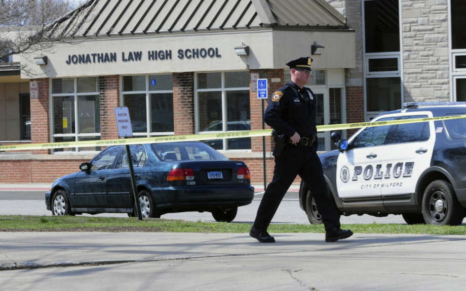 Police remain on scene at Jonathan Law High School after a 16-year-old girl was stabbed to death in Milford, Conn., Friday, April 25, 2014. A teenage boy is in custody, and police are investigating whether the attack stemmed from her turning down an invitation to be his prom date. (AP Photo/The New Haven Register, Peter Hvizdak) MANDATORY CREDIT