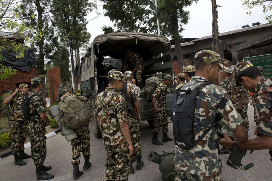 """Nepalese army soldiers prepare to leave for a rescue mission to the site where the suspected wreckage of a U.S. Marine helicopter, that disappeared earlier this week while on a relief mission in the earthquake-hit Himalayan nation, was spotted, in Kathmandu, Nepal, Friday, May 15, 2015. Nepalese rescuers on Friday found three bodies near the wreckage of the chopper that was carrying six Marines and two Nepalese army soldiers. The U.S. Marines said they were sending their own rescue team to assess the wreckage and determine if it was the missing helicopter, the UH-1 """"Huey."""" (AP Photo/Bernat Armangue)"""