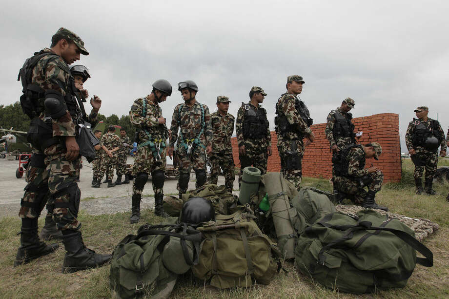 "Nepalese army soldiers prepare to leave for a rescue mission to the site where the suspected wreckage of a U.S. Marine helicopter, that disappeared earlier this week while on a relief mission in the earthquake-hit Himalayan nation, was spotted, in Kathmandu, Nepal, Friday, May 15, 2015. Nepalese rescuers on Friday found three bodies near the wreckage of the chopper that was carrying six Marines and two Nepalese army soldiers. The U.S. Marines said they were sending their own rescue team to assess the wreckage and determine if it was the missing helicopter, the UH-1 ""Huey."" (AP Photo/Niranjan Shrestha)"